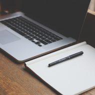Travailler avec un ordinateur portable. Carnet d'écriture et stylo
